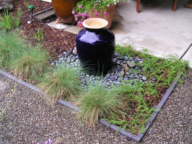 black vase and bunchgrass in bordered bed
