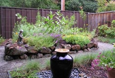 Black vase fountain in front of flowerbed